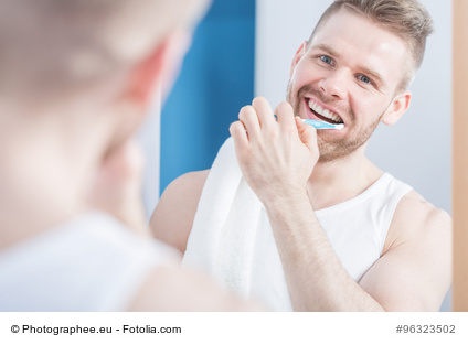 Attractive guy with perfect smile brushing his teeth